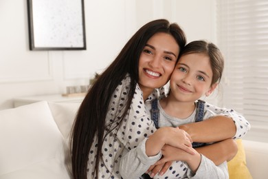 Portrait of happy mother and daughter hugging at home. Single parenting
