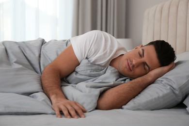 Man sleeping in bed with grey linens at home