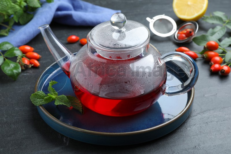 Teapot with aromatic rose hip tea and fresh mint on black table