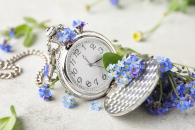 Beautiful blue forget-me-not flowers with pocket watch on light stone table, closeup