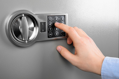 Man opening steel safe with electronic combination lock, closeup