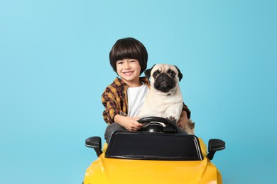 Little boy with his dog in toy car on light blue background