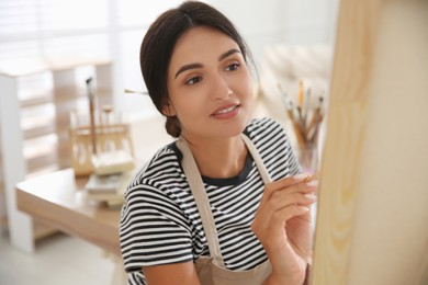 Young woman drawing on canvas with brush indoors