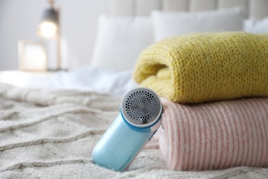 Modern fabric shaver and woolen sweaters on bed indoors, closeup. Space for text