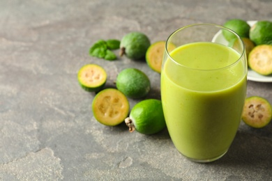 Fresh feijoa smoothie in glass on grey table, closeup. Space for text
