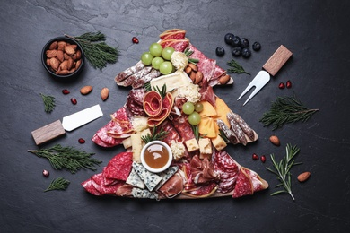 Fir tree shaped board with different appetizers and sauce on black table, flat lay