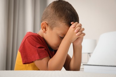 Cute little boy with hands clasped together saying bedtime prayer at home