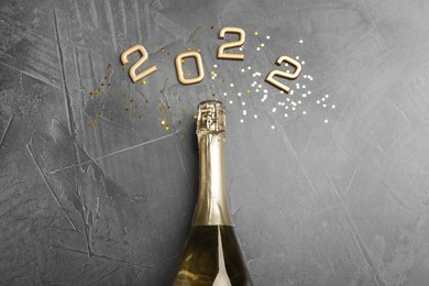 Bottle of sparkling wine, gold confetti and number 2022 on grey background, flat lay. Happy New Year