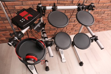 Modern electronic drum kit with headphones near red brick wall indoors, above view. Musical instrument