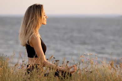 Young woman meditating near river on sunny day, space for text
