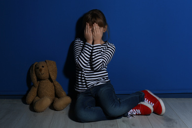 Abused little girl crying near blue wall. Domestic violence concept