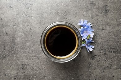 Delicious chicory drink and flowers on grey table, flat lay