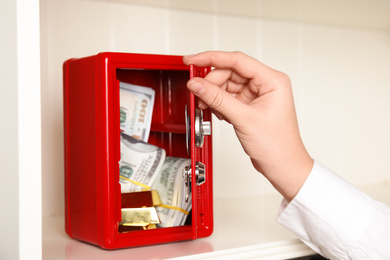 Woman opening red steel safe on shelf, closeup