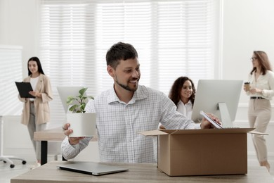 New coworker unpacking box with personal items at workplace in office