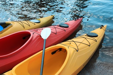 Modern kayaks with paddle on beach near river. Summer camp activity