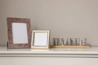 Empty photo frames and candles on table indoors, space for text