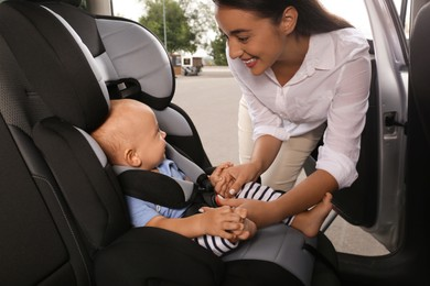 Mother fastening her son in child safety seat inside car