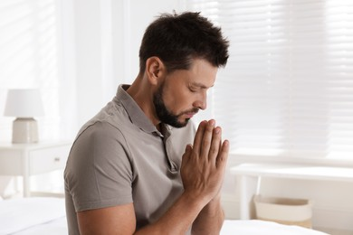 Religious man with clasped hands praying at home
