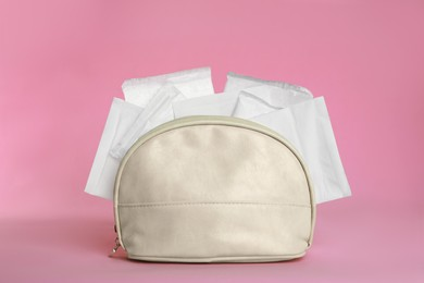 Bag with menstrual pads on pink background