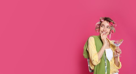 Young housewife with glass of martini on pink background. Space for text