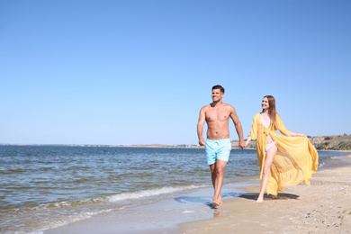 Woman in bikini and her boyfriend on beach, space for text. Happy couple