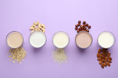 Different vegan milks and ingredients on violet background, flat lay