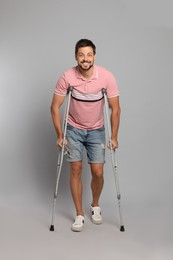 Full length portrait of man with crutches on grey background
