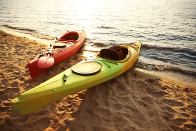 Colorful kayaks near water on river beach at sunset. Summer camp activity