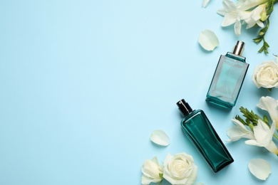 Flat lay composition with different perfume bottles and flowers on light blue background, space for text
