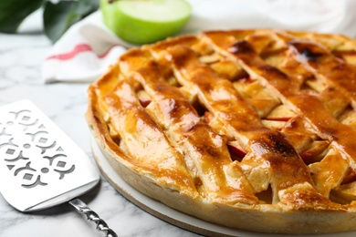 Fresh traditional apple pie on white marble table, closeup