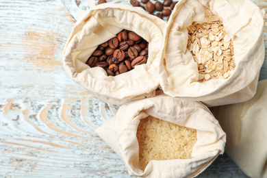 Cotton eco bags with cereals and coffee beans on wooden table, flat lay