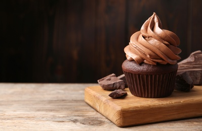 Delicious cupcake with cream and chocolate pieces on wooden table, closeup. Space for text