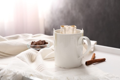 Cup with drip coffee bag and cinnamon on white table, closeup