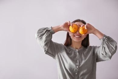Woman with fresh tangerines on light grey background. Space for text