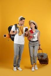 Couple of tourists with tickets, passports and luggage on yellow background