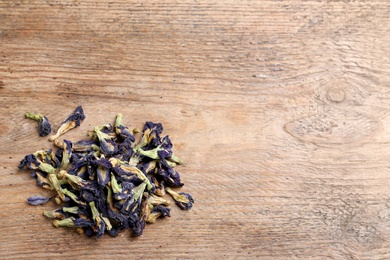 Pile of dry organic blue Anchan on wooden table, flat lay with space for text. Herbal tea