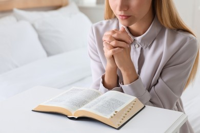 Religious young woman with Bible praying in bedroom, closeup