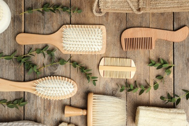 Flat lay composition with hair brushes and combs on wooden background