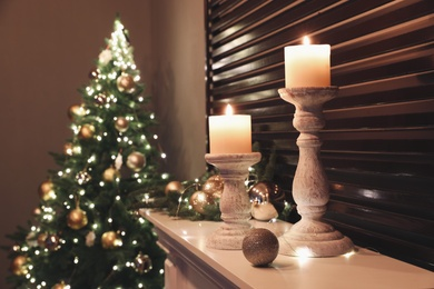 Burning candles and Christmas decor on white mantelpiece indoors