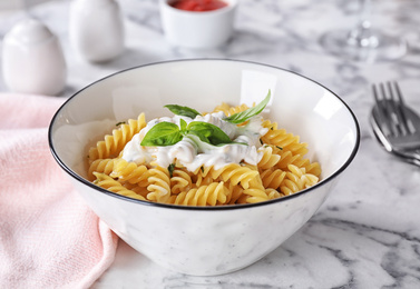 Delicious pasta with sauce served on white marble table
