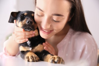 Woman with cute puppy indoors. Lovely pet