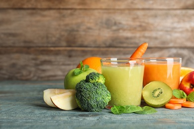 Glasses of delicious juices and fresh ingredients on blue wooden table. Space for text