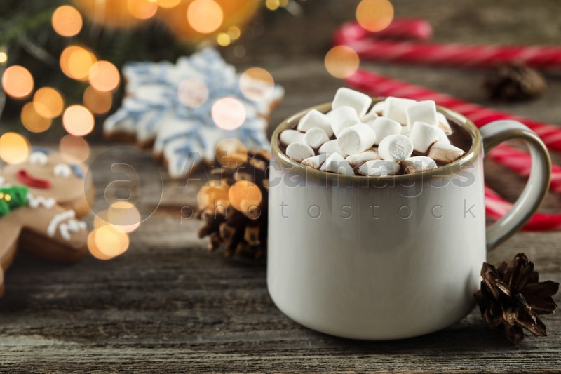 Delicious hot chocolate with marshmallows and Christmas decor on wooden table, closeup. Space for text