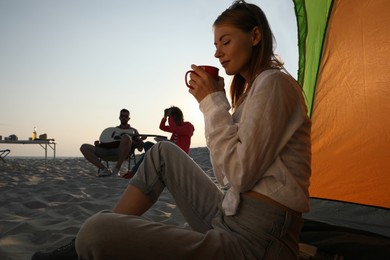 Friends resting on sandy beach. View from camping tent