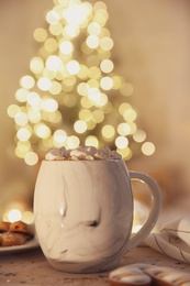 Tasty hot drink with marshmallows on table against Christmas lights. Space for text