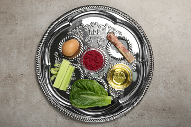 Passover Seder plate (keara) with symbolic meal on grey table, top view. Pesah celebration