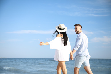 Happy young couple walking at beach on sunny day