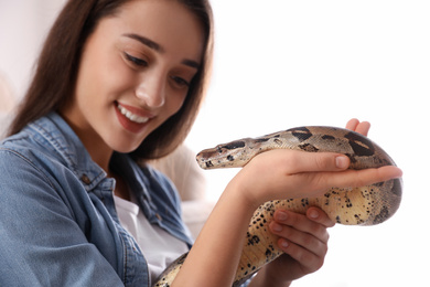 Young woman with her boa constrictor at home. Exotic pet