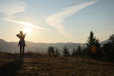 Woman enjoying sunrise in mountains, back view. Space for text