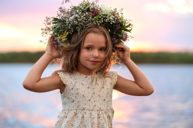 Cute little girl wearing wreath made of beautiful flowers near river at sunset